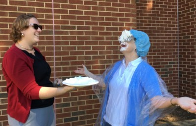 Diane Valade laughs after a student hist her int he face with a pie. Photography by Teriney Grooms